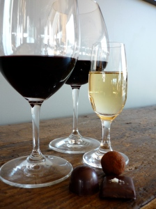 Three glasses of wine and three artisanal chocolates displayed on wooden table