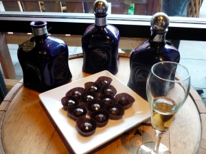 A glass of Single Barrel Reposado Tequila with a tray of chocolates and three bottles of Reposado resting on the actual barrel they came from